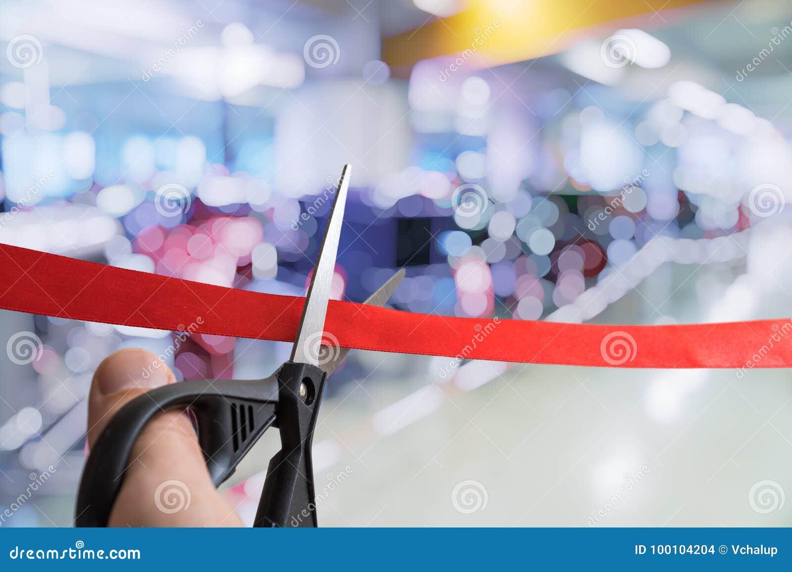 As tesouras estão cortando a fita vermelha Cerimônia de inauguração ou evento