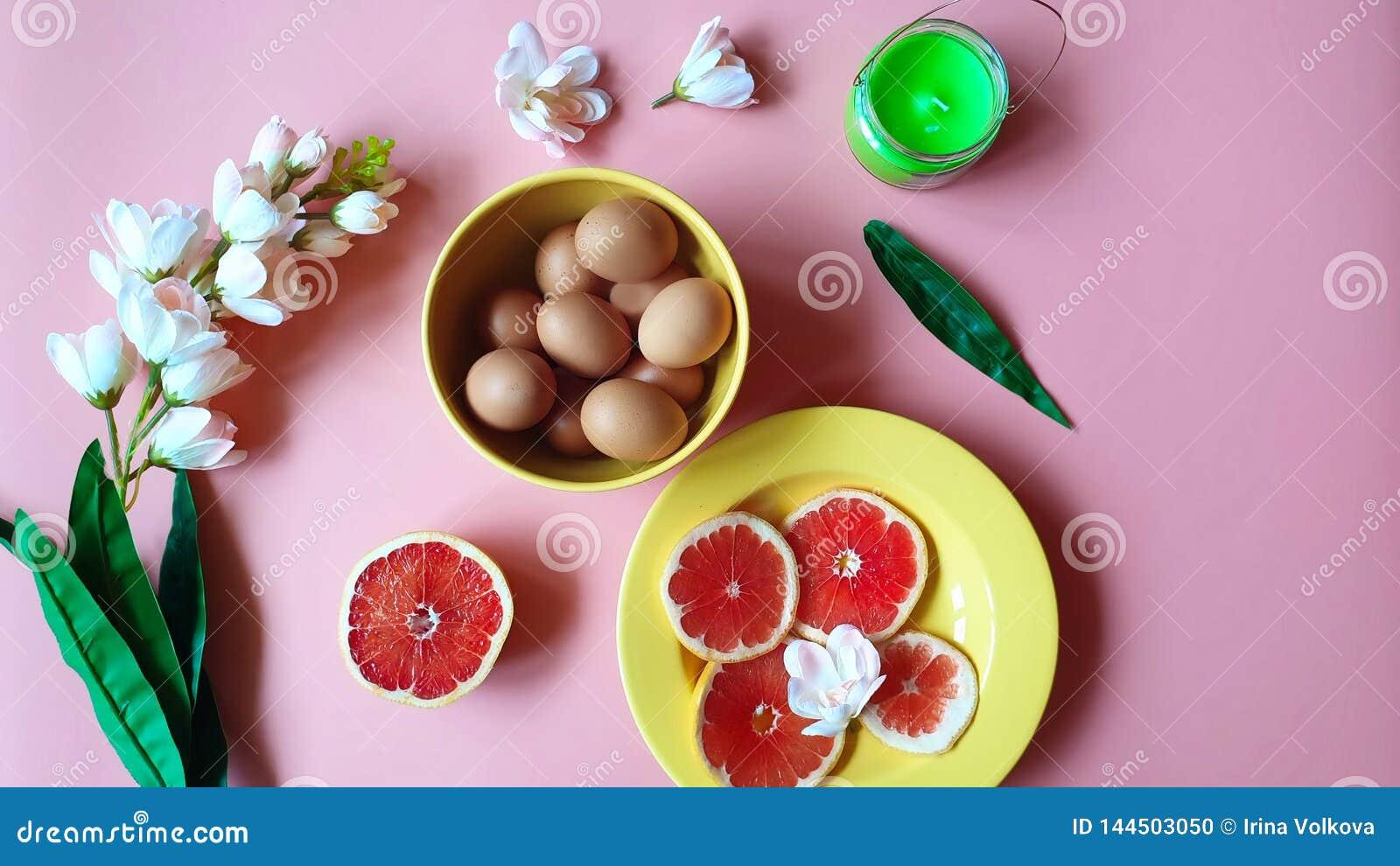 As toranjas vermelhas dos ovos da páscoa felizes picam a placa amarela da vela verde branca do aroma das flores da maçã no fundo