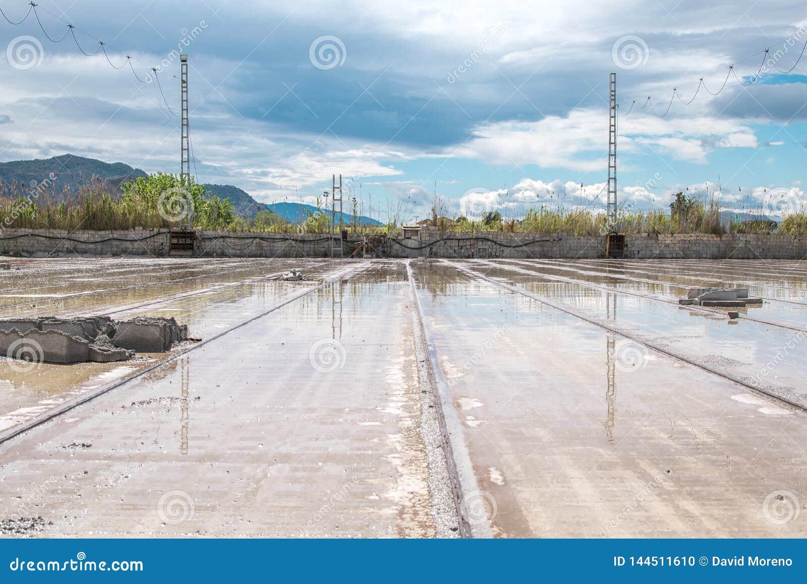 As trilhas cobrem com a poça da chuva em uma construção de casa da fábrica