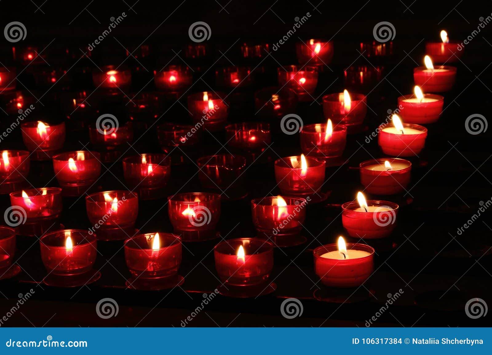 As velas vermelhas com incandescência iluminam-se na escuridão na igreja Fundo da paz e da esperança Conceito da religião