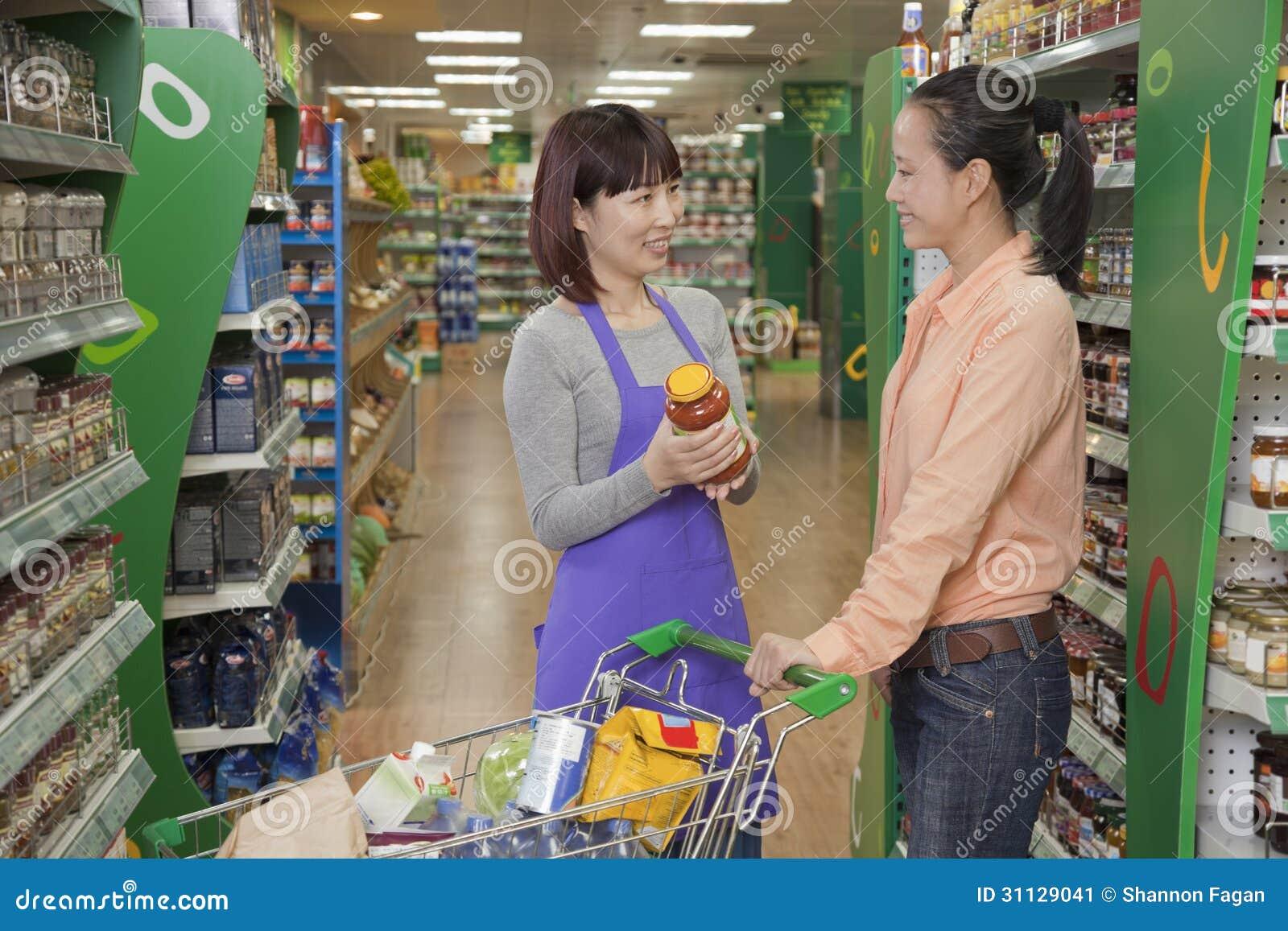 As vendas clerk a ajuda das mulheres, guardarando o frasco no supermercado, Pequim