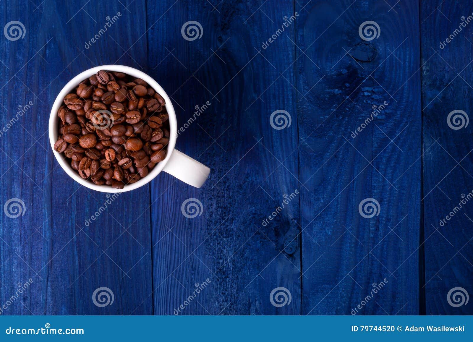 Asalte por completo de los granos de café en fondo de madera azul