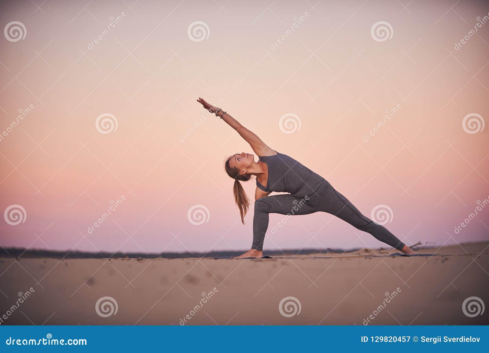 Asana bonito Utthita Parshvakonasana da ioga das práticas da jovem mulher - estenda a pose do ângulo lateral no deserto no por do