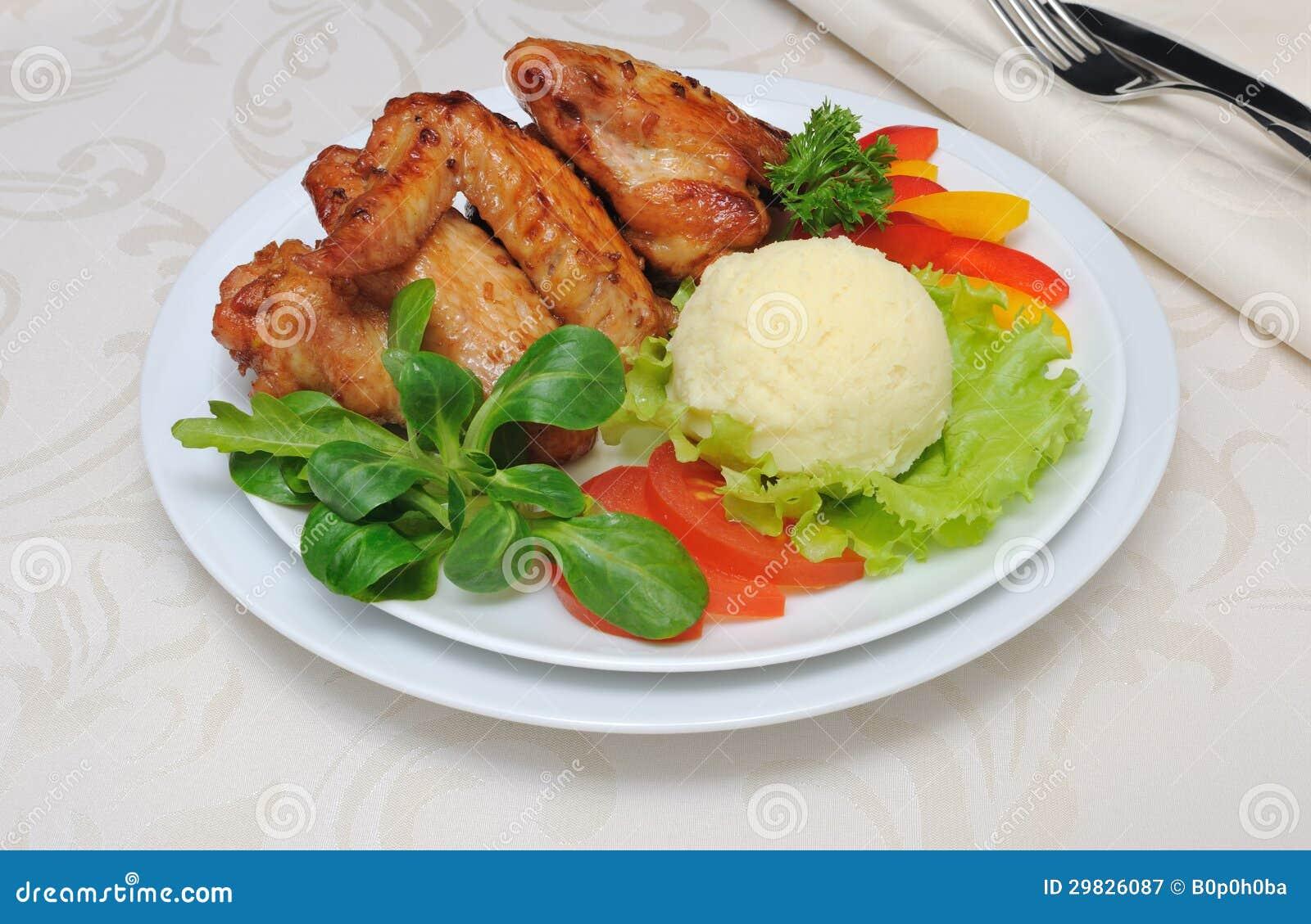 Asas de galinha cozidas com alho e batatas e vegetais