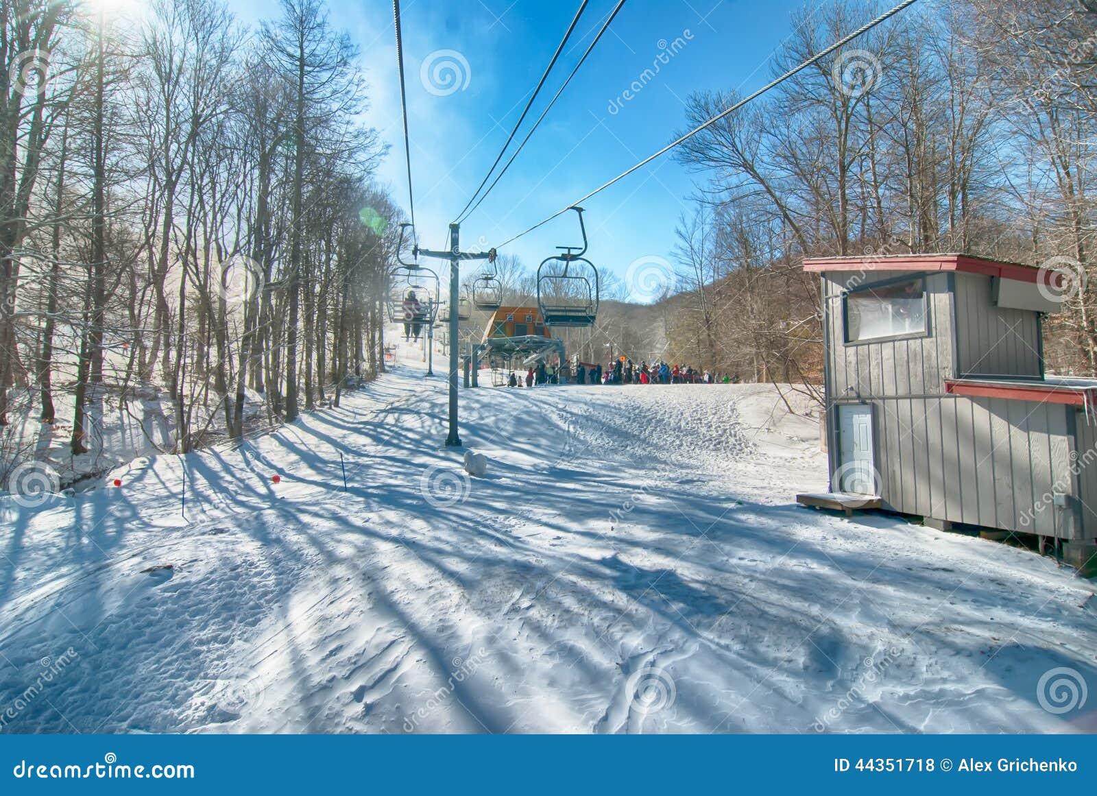 Ascensore di sci con i sedili che superano la montagna