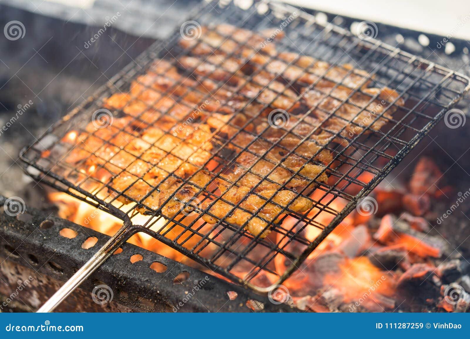 Ase a la parilla la carne que cocina en el fuego - el ingrediente del cha del bollo la sopa de fideos vietnamita famosa con la ca