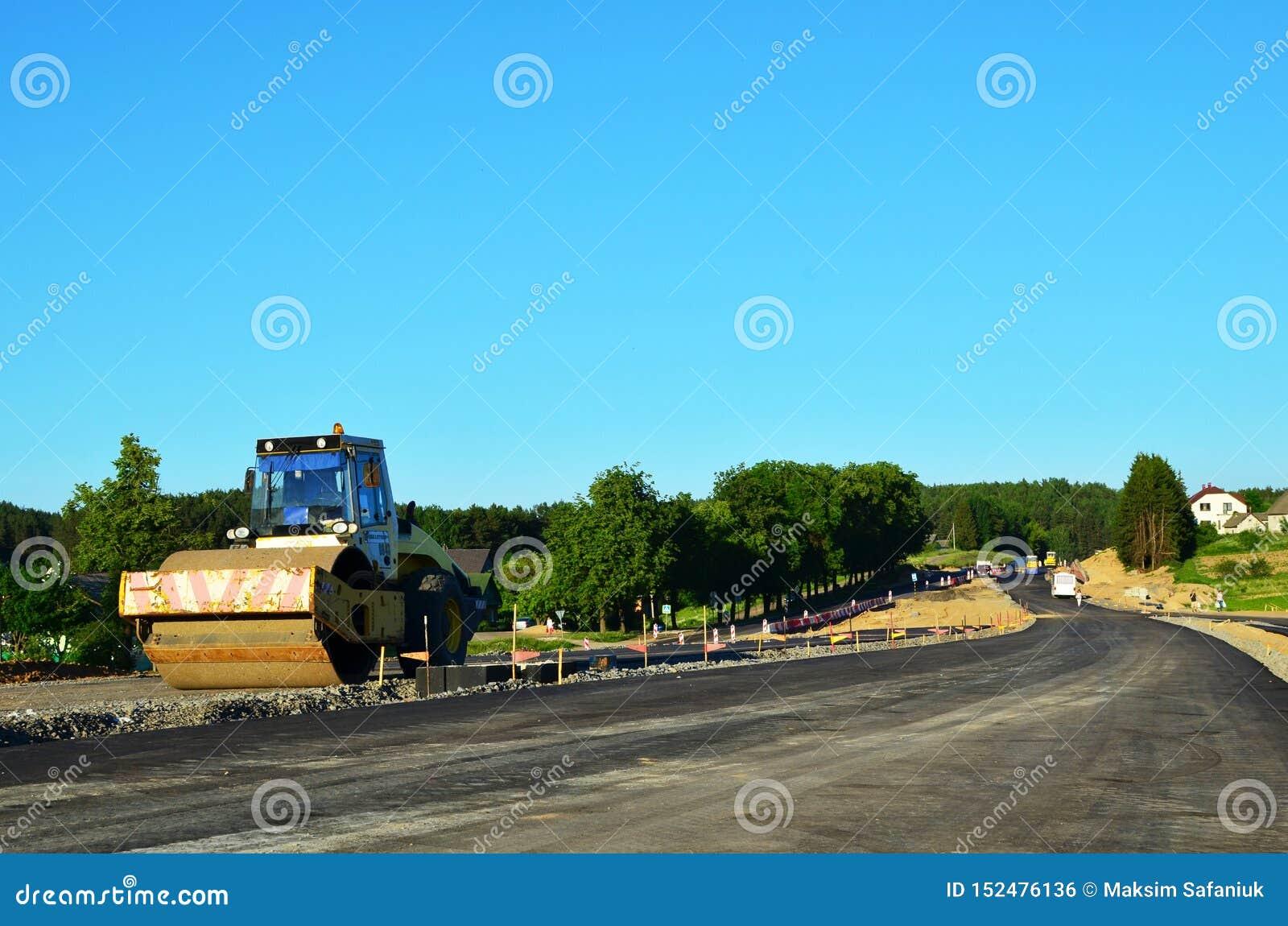 Asfaltera byggnationer med kommersiell reparationsutrustning V?grullar som j?mnar ny asfalttrottoar