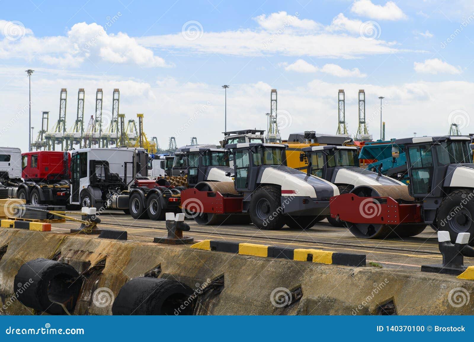 Asfaltera rullen och lastbilar som väntar päfyllning på ett skepp för import eller export