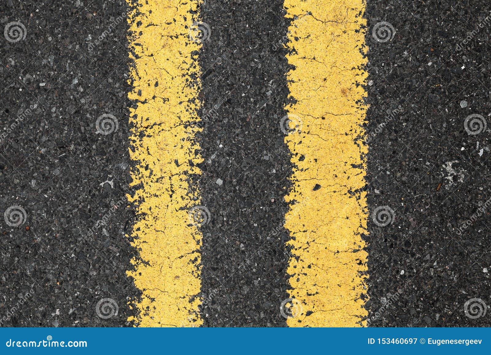 Asfaltera vägen med den gula dubbla delande linjen