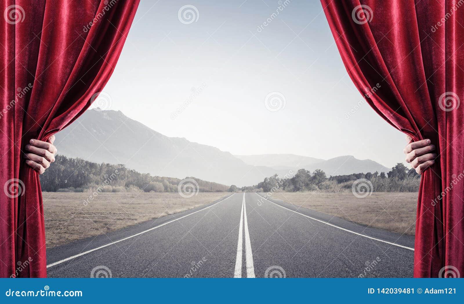 Asfalto la carretera detrás de la cortina roja y dé sostenerla