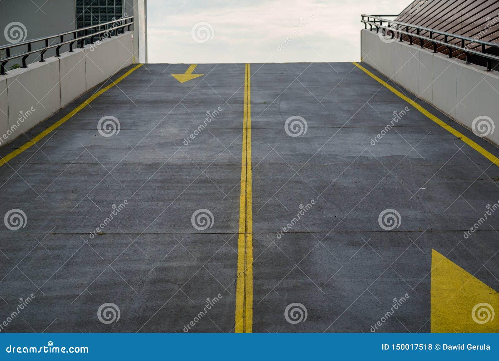 Asfaltowa droga, podjazd kondygnacja parking, garaż z grunge powierzchni teksturą i kontrastujący żółty kolor ruch drogowy,