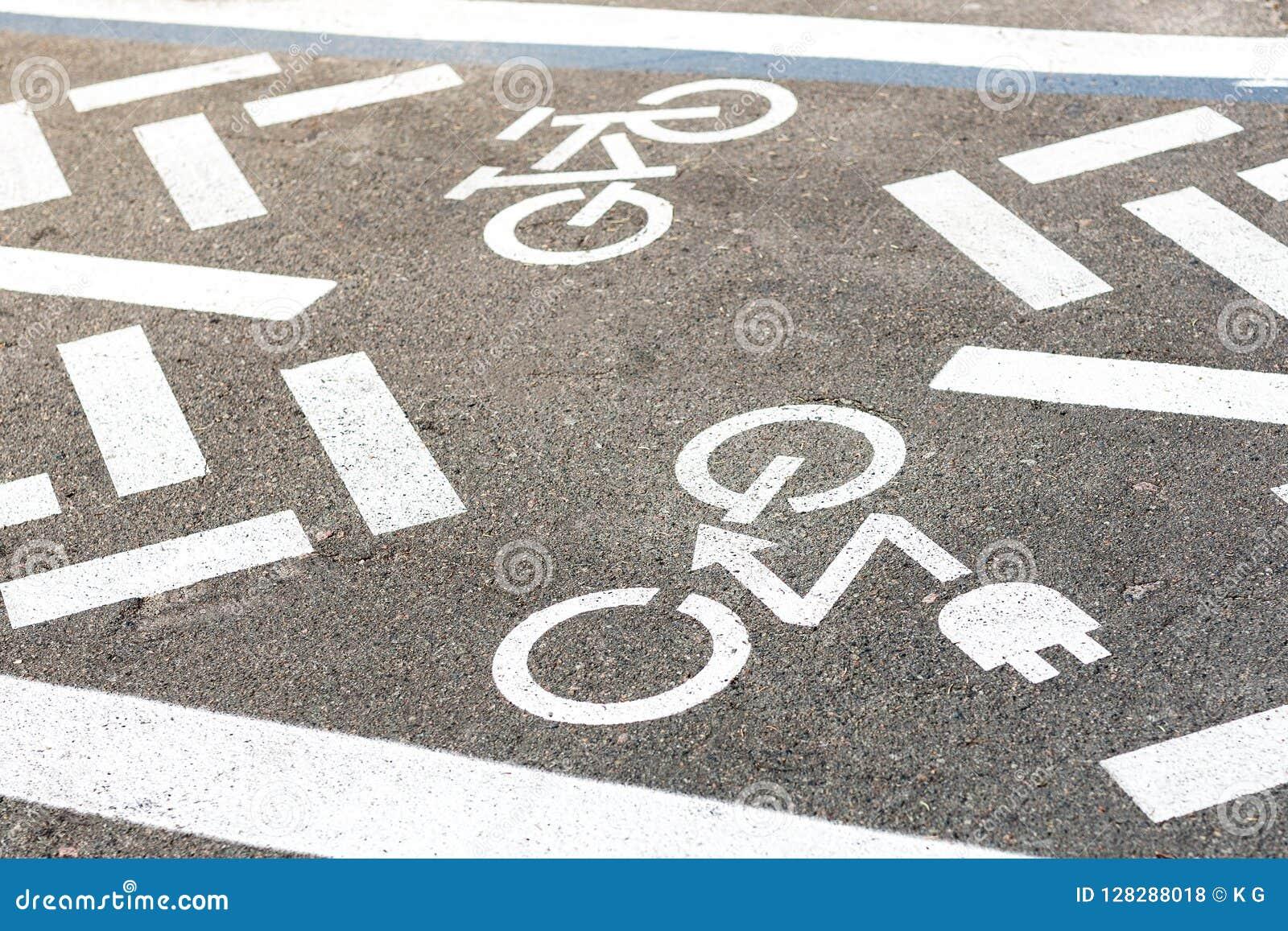 Asfaltowa droga z rowerowym i elektrycznym przewiezionym pasem ruchu Jeździć na rowerze emisja pojazdów bielu znaka na podłoga i