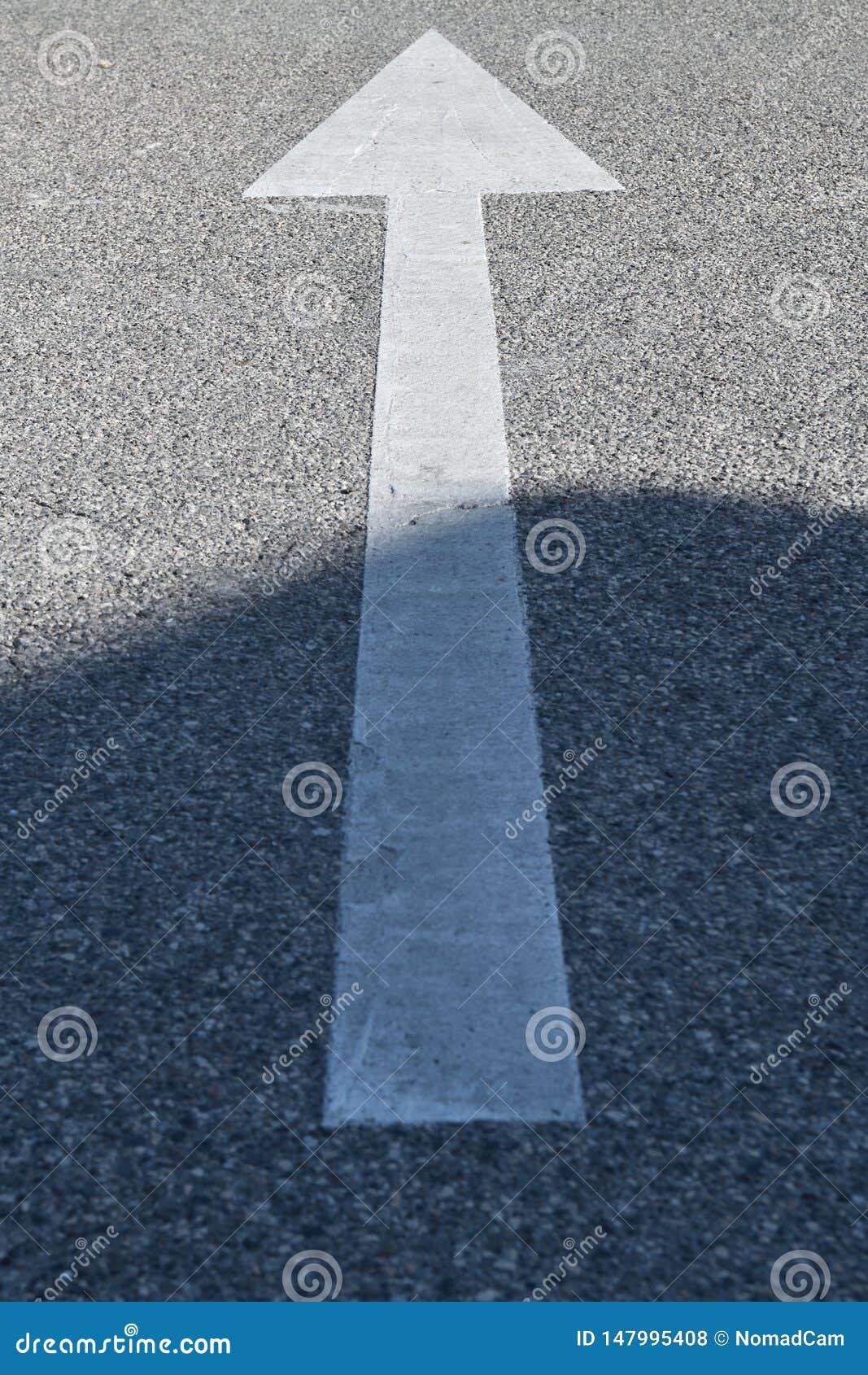 Asfaltowy znak: biała strzała na betonowej teksturze