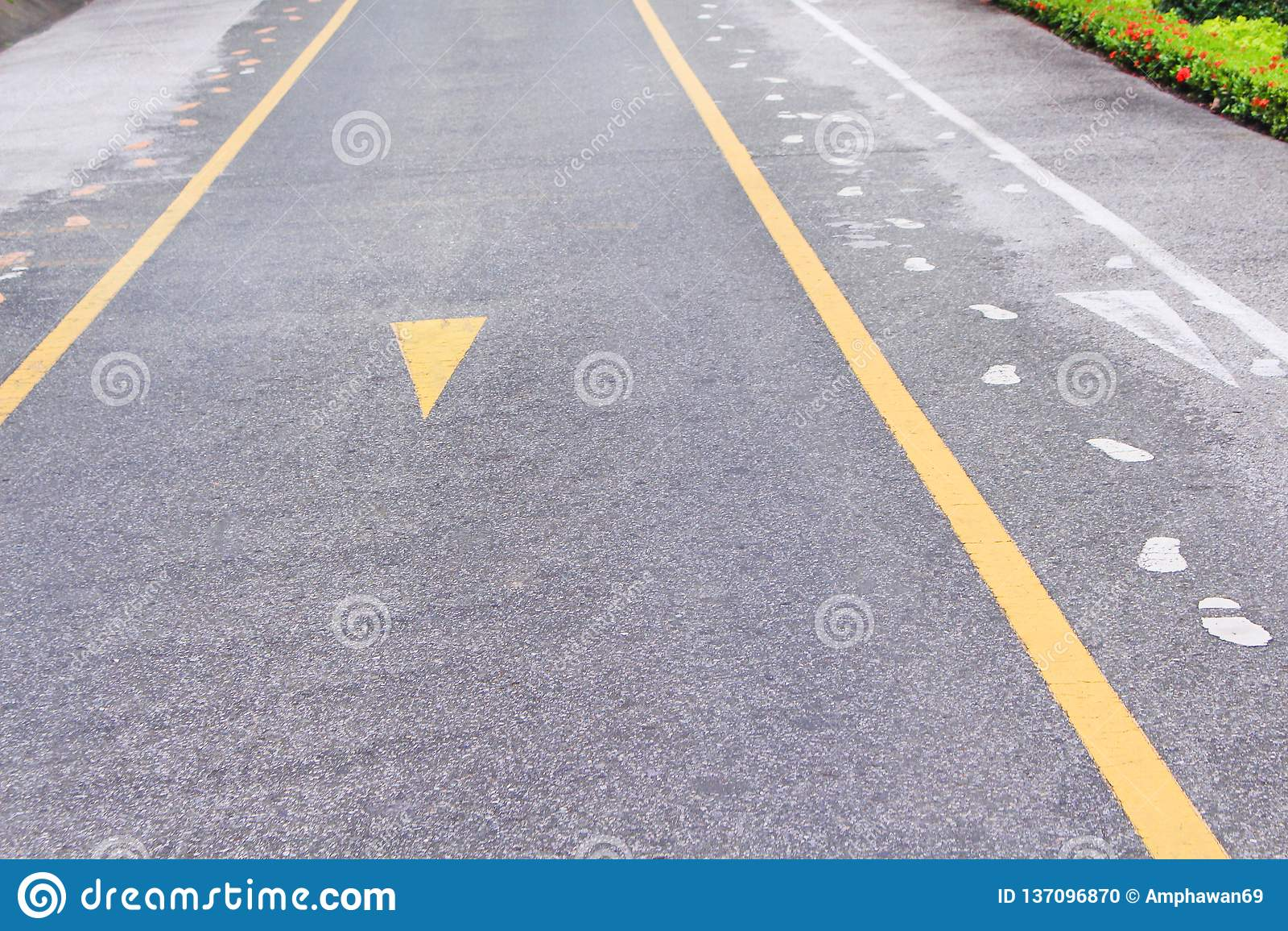 Asfaltweg met twee gele lijnen en de samenvatting van het stoepteken op achtergrond