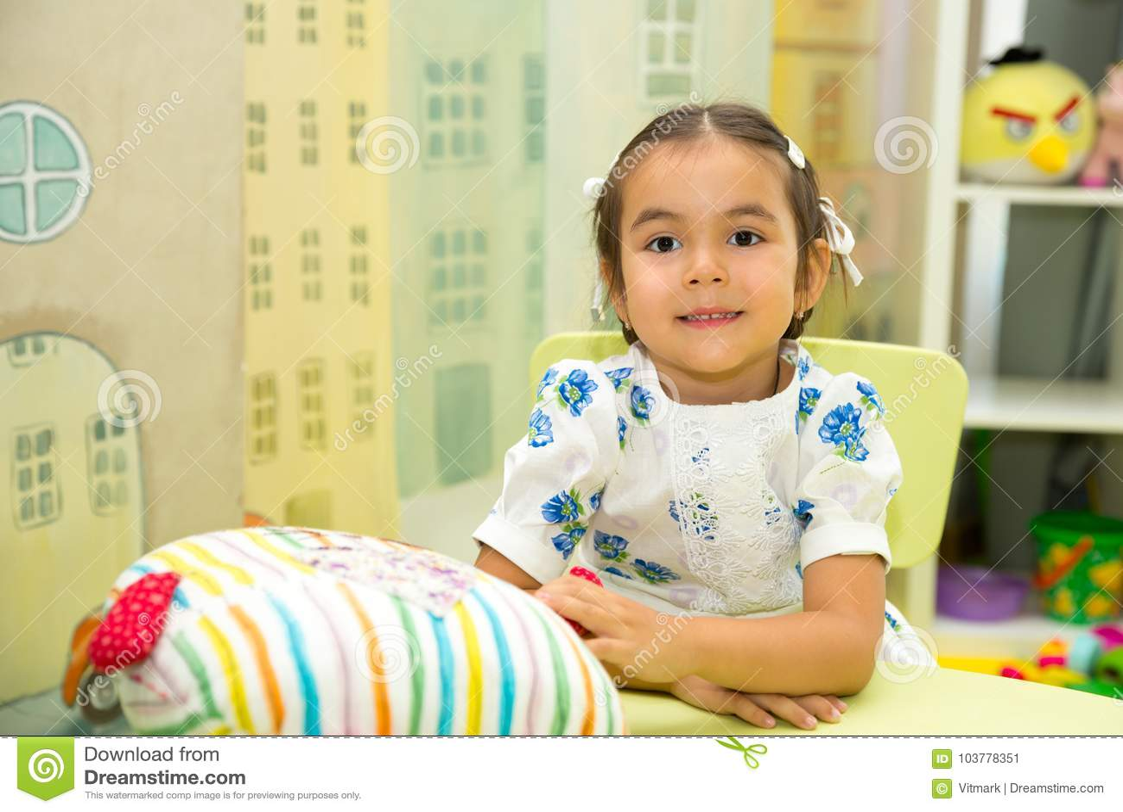 Asiático adorable, muchacha del niño del Kazakh en sitio del cuarto de niños Niño en guardería en clase del preescolar de Montess