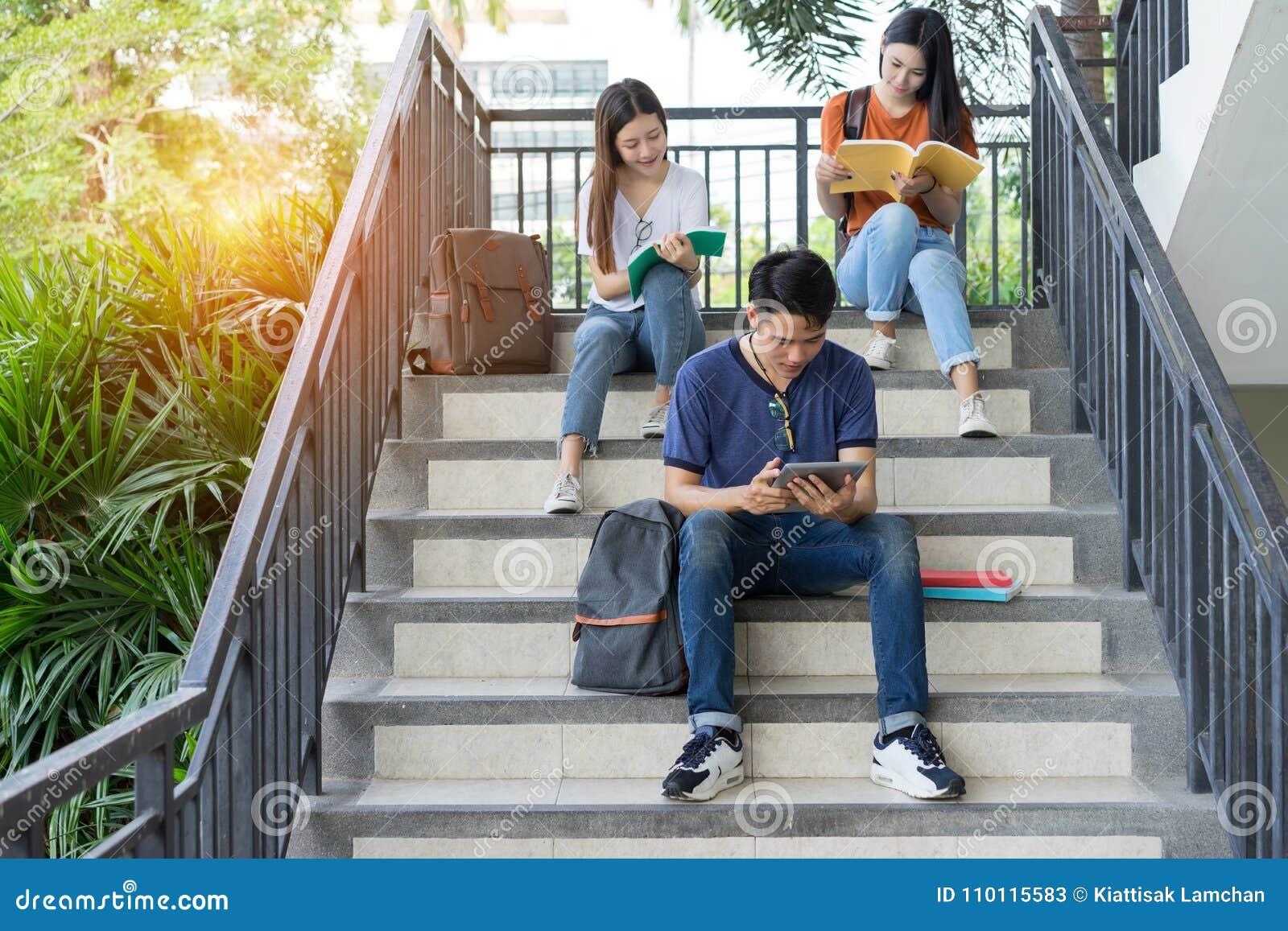 Asiático da universidade dos estudantes que lê junto o estudo do livro