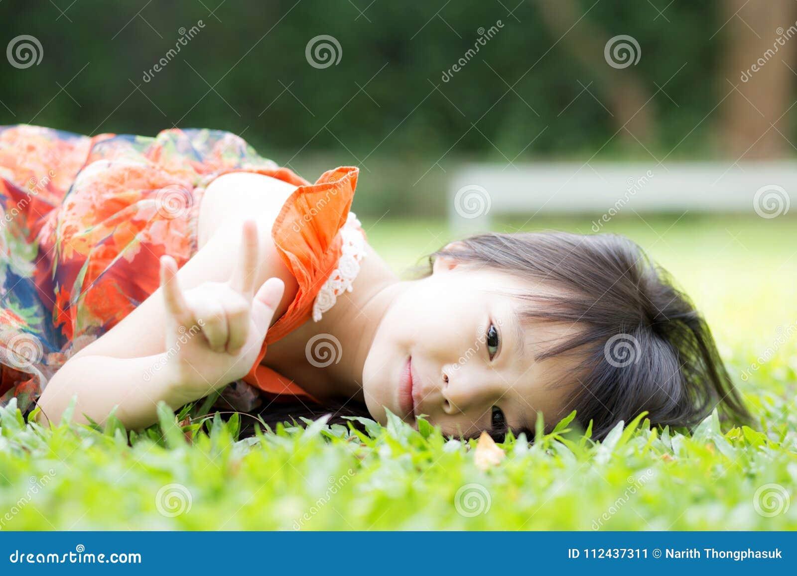 Asiático hermoso de la niña del retrato de una mentira sonriente en hierba verde en el parque