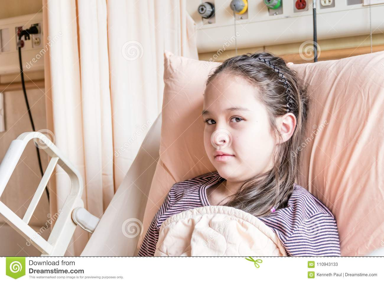 Asian American tween girl in hospital bed
