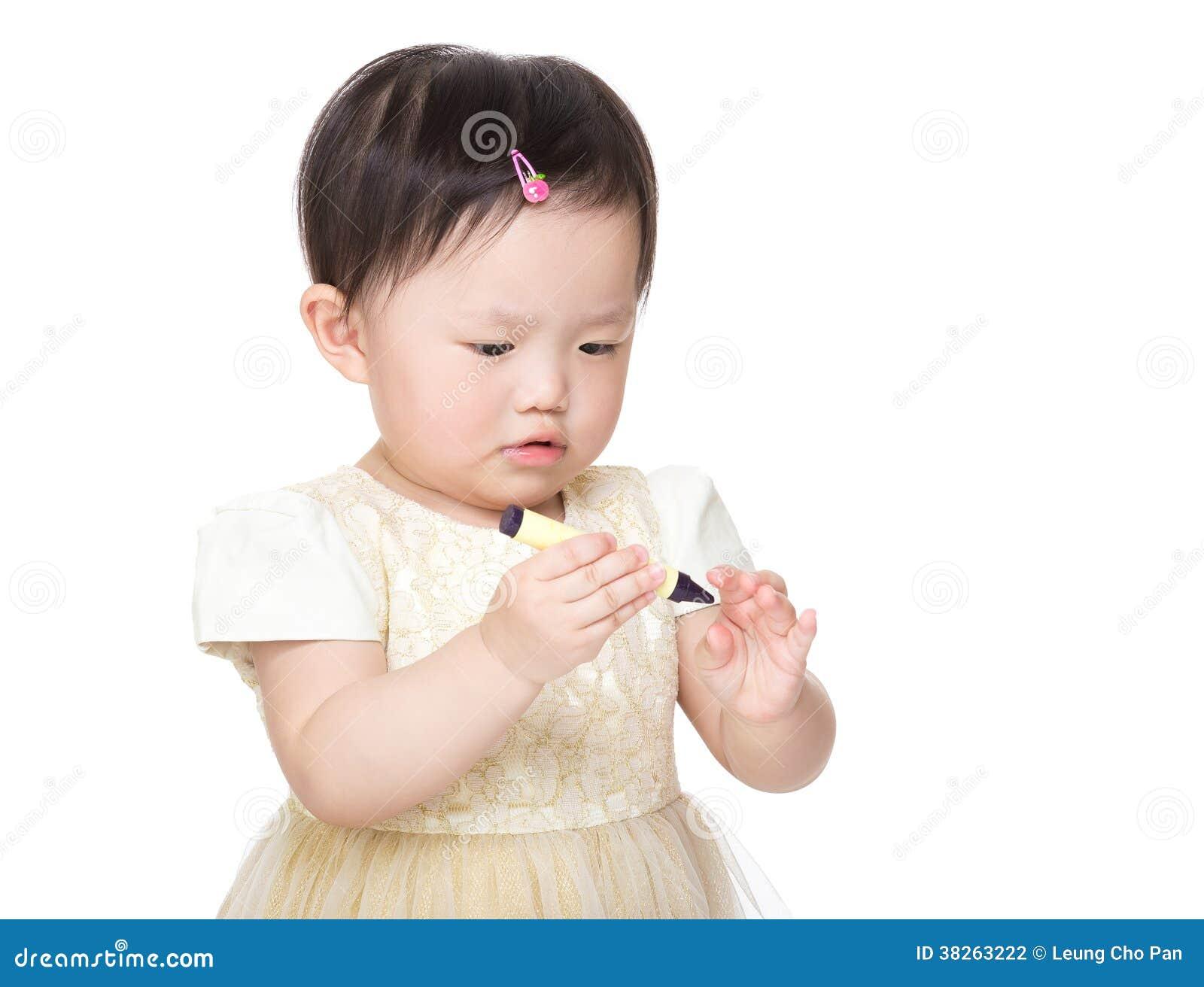 Asian baby girl holding crayon