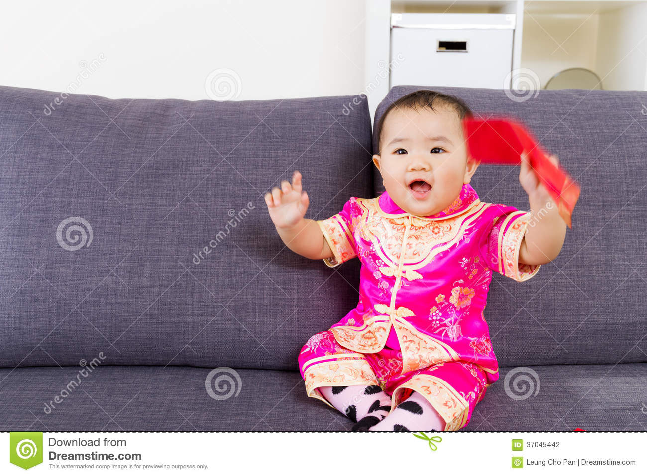 asian baby holding red pocket with traditional chinese