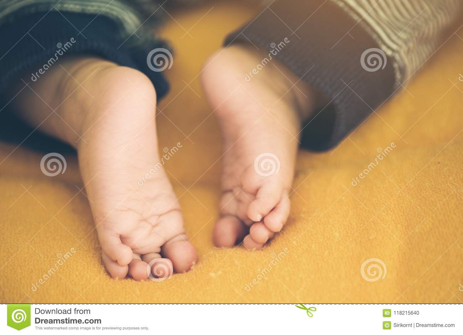 asian baby on a white blanket - tiny baby feet closeup stock photo