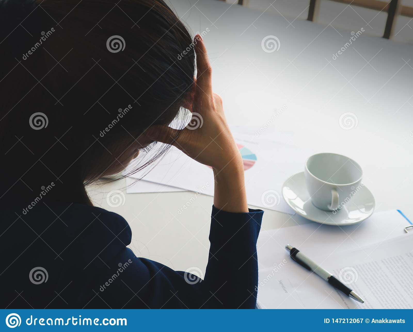 Asian long hair beautiful business woman in navy blue suit strain with work util headache in her office. Have coffee cup, pen, rep
