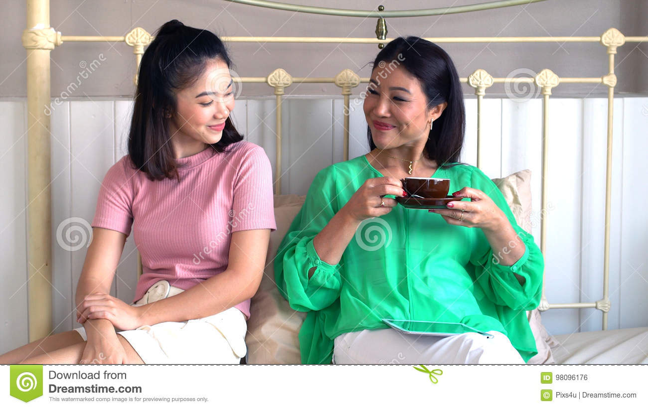 asian beautiful mother and pretty teenage daughter with tablet stock