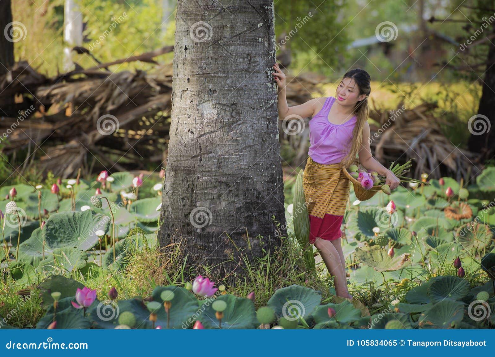 Asian beautiful woman walking in lotus field.