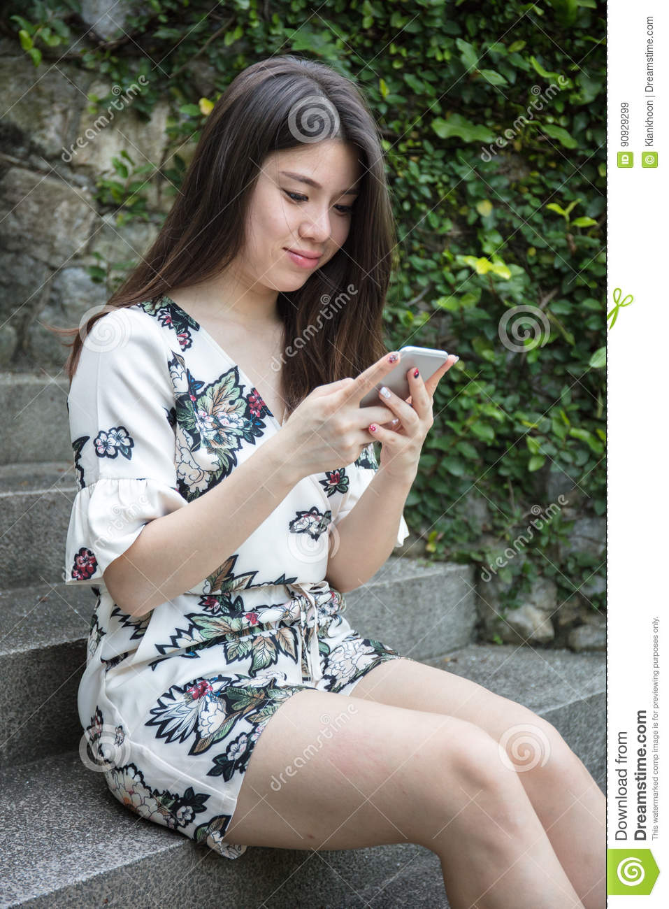 Asian beautiful young woman playing with smart phone