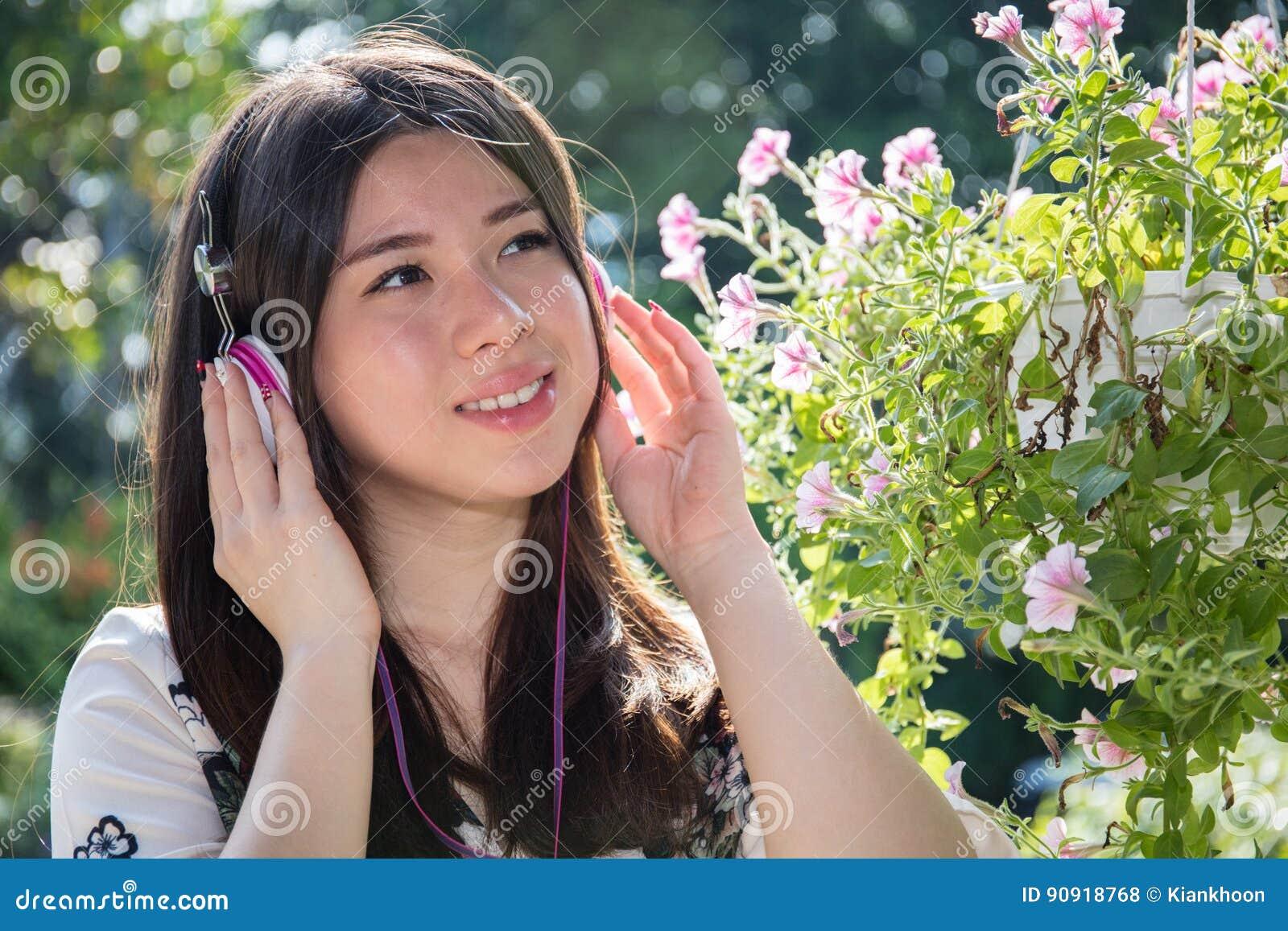 Asian beautiful young woman wearing headphones in the garden
