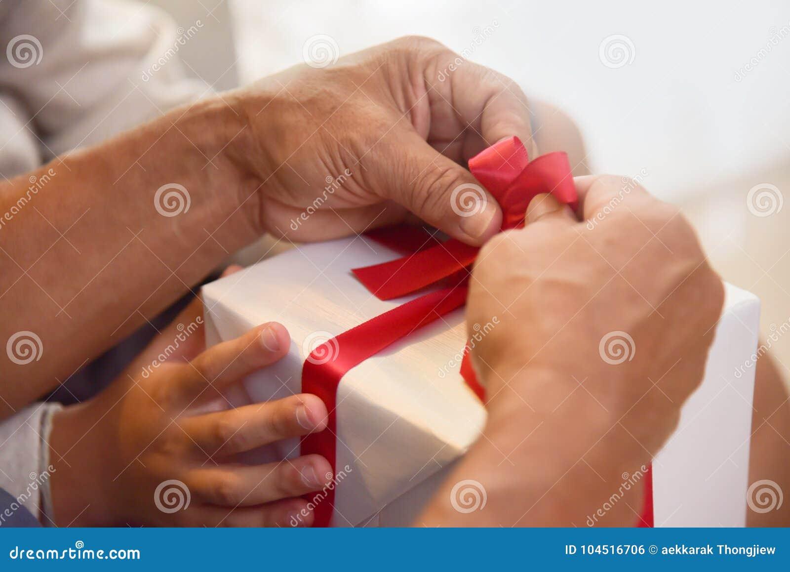 Asian Boy And Elderly Man Holding On Red Ribbon Of White Gift Bo