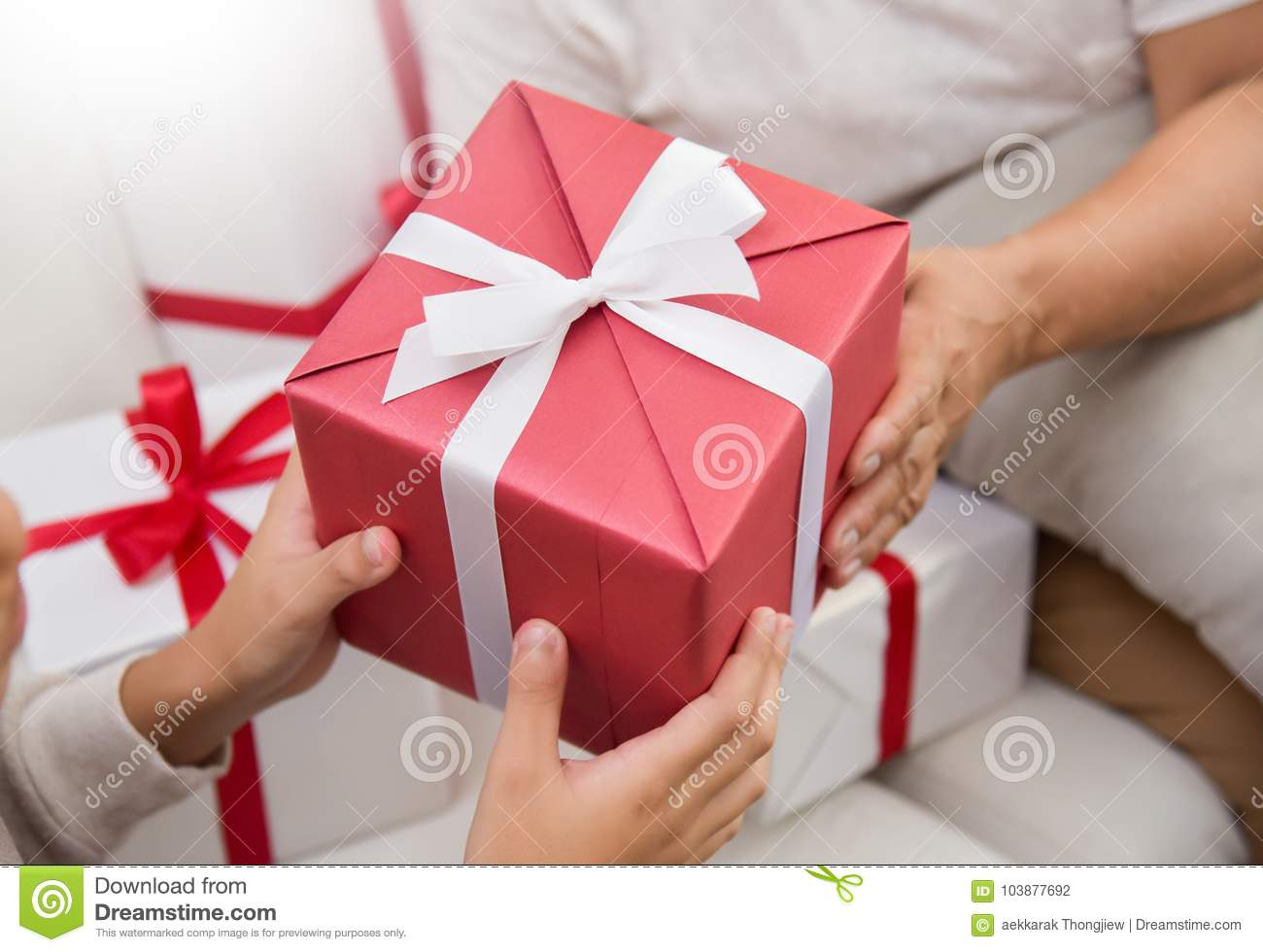 Asian Boy Giving A Red Gift Box To Elderly Woman Stock Photo