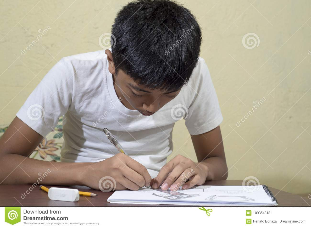 Asian boy learning and practicing to draw 3D shapes on drawing notebook