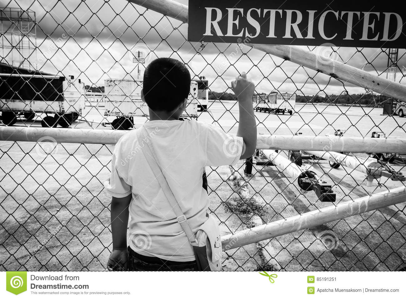 asian boy sad and standing alone at the door of airport a stock