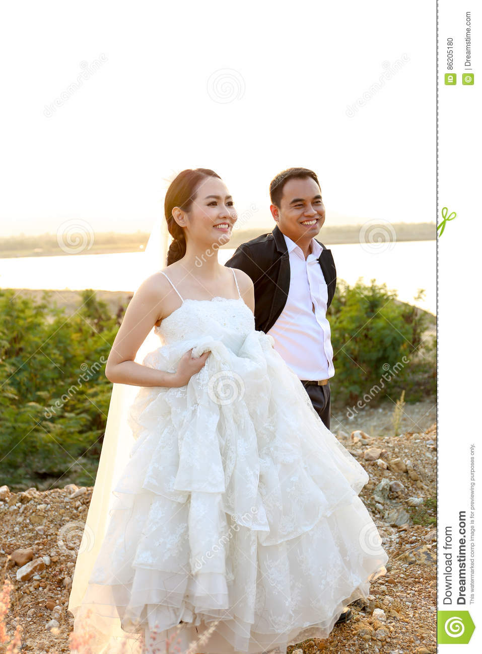 Asian Bride And Groom In Wedding Dresses Against The Sunset Scene ...