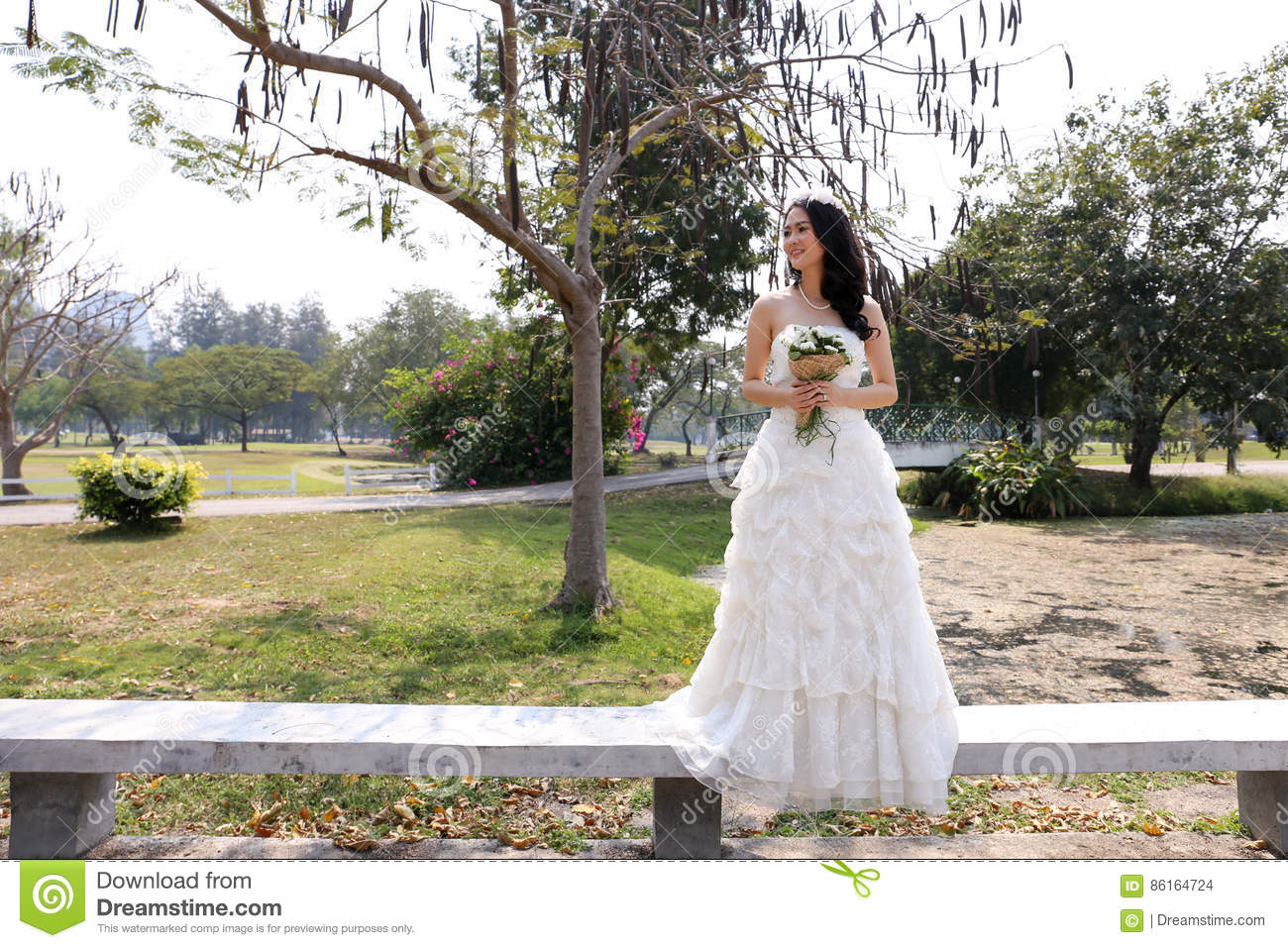 Asian Bride In White Bridal Gown Holding A Lovely Bouquet In A ...