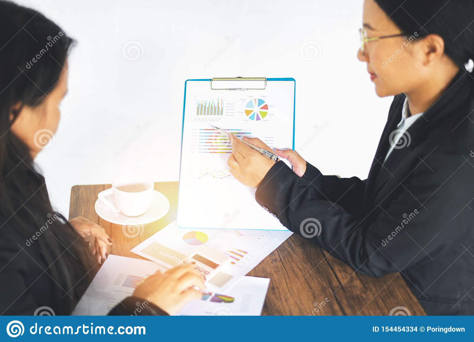 Asian business women working present the report graph financial information at the meeting in office the table desk - checking