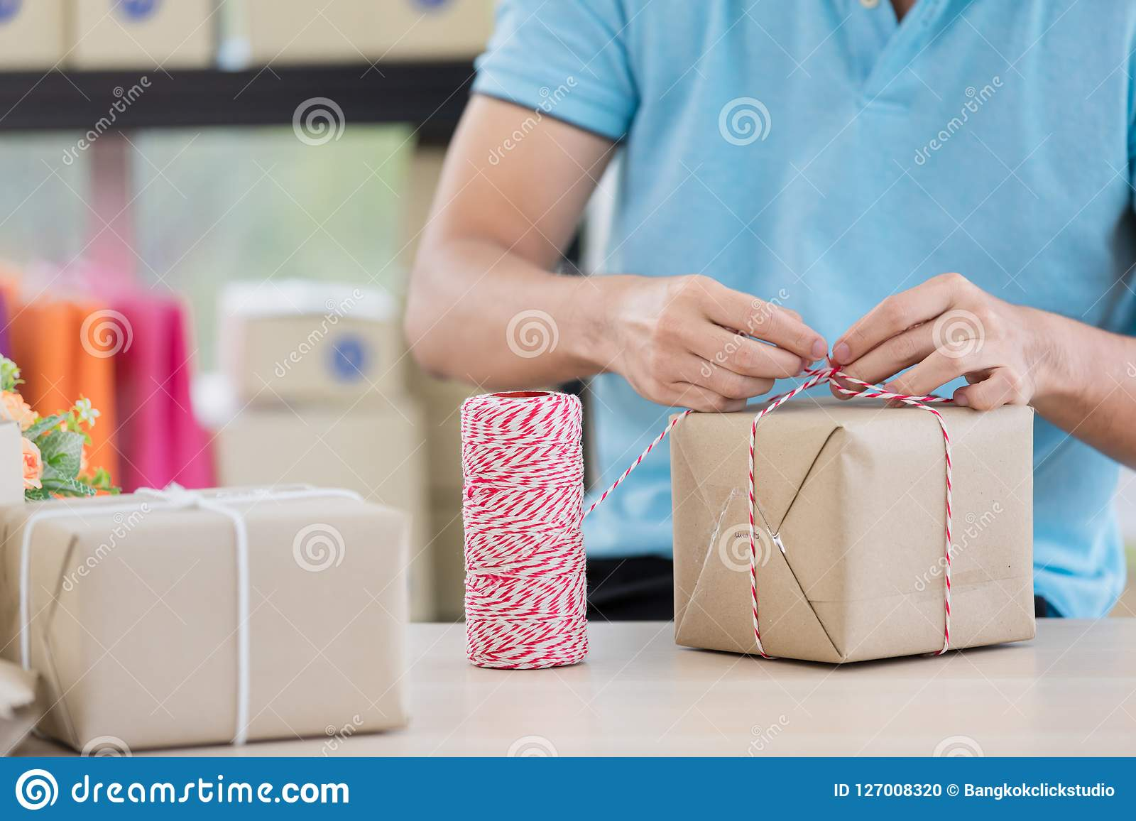 Asian businessman in casual shirt was is packing parcels, working in simple house office look like doing startup business.
