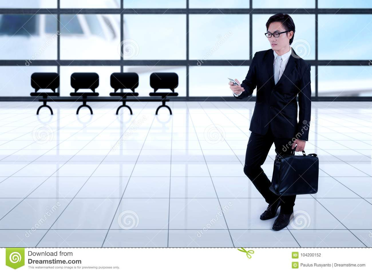 Asian businessman with smartphone in the airport