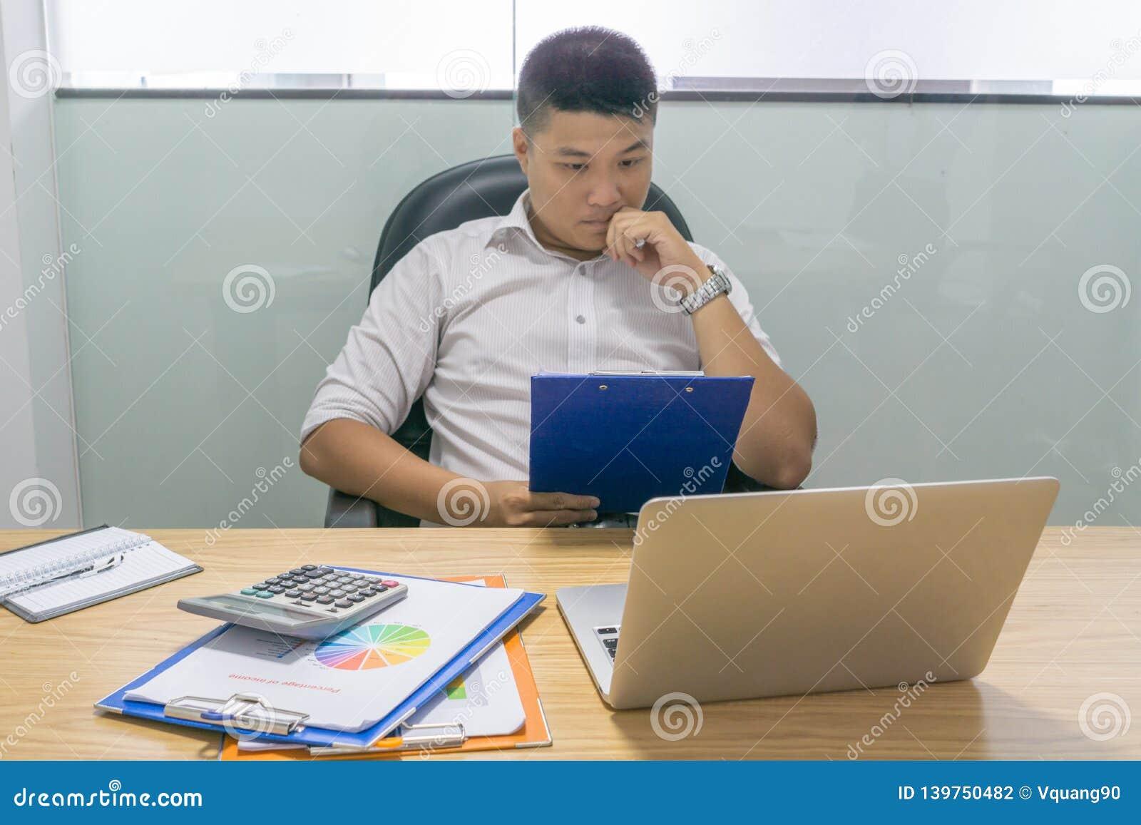 Asian businessman reading financial report document