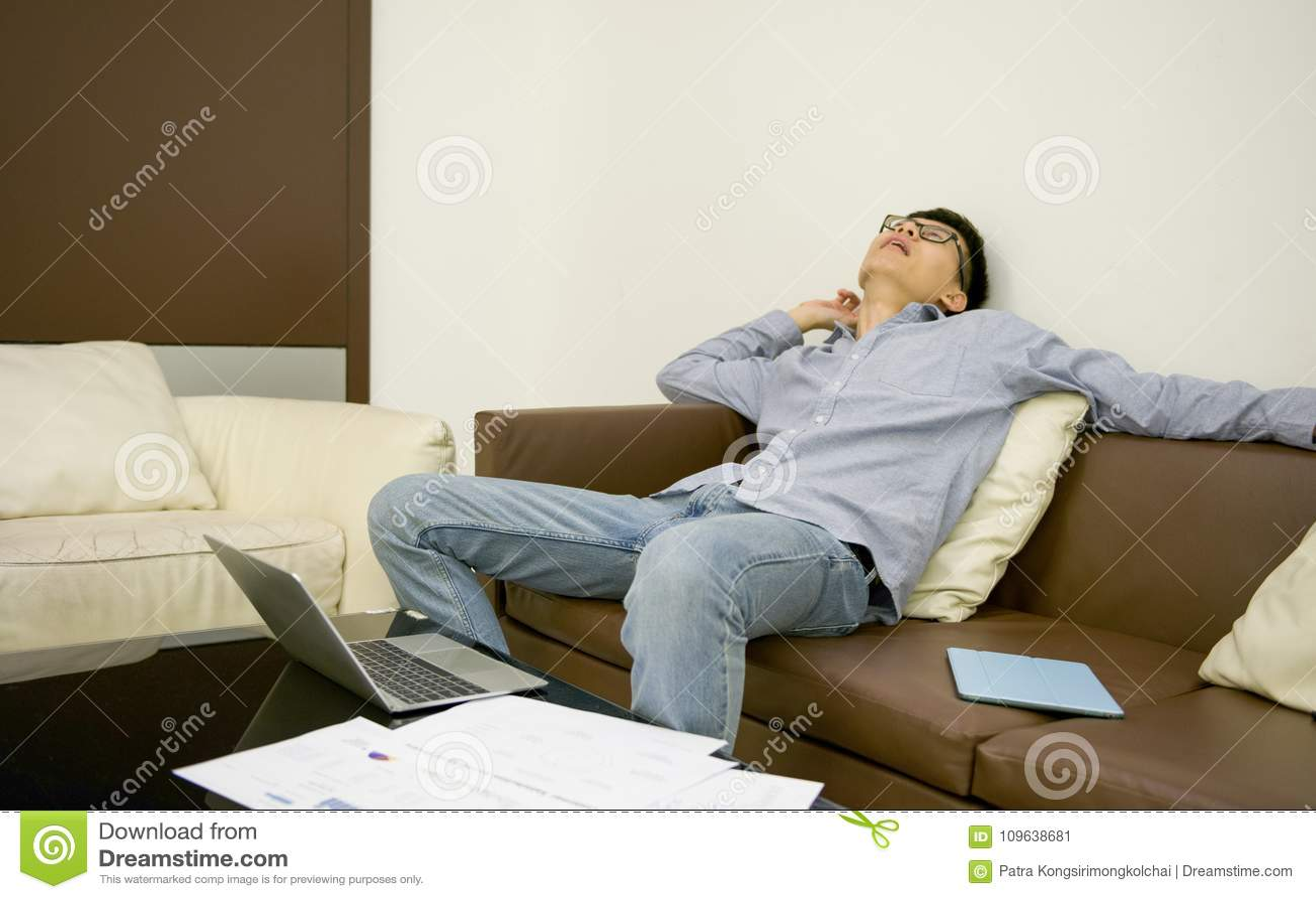 Asian Businessman Sleeping On Sofa In Living Room At Night.