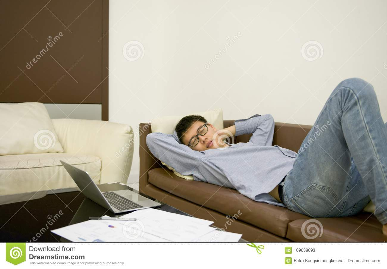 Asian Businessman Sleeping On Sofa In Living Room At Night Stock ...