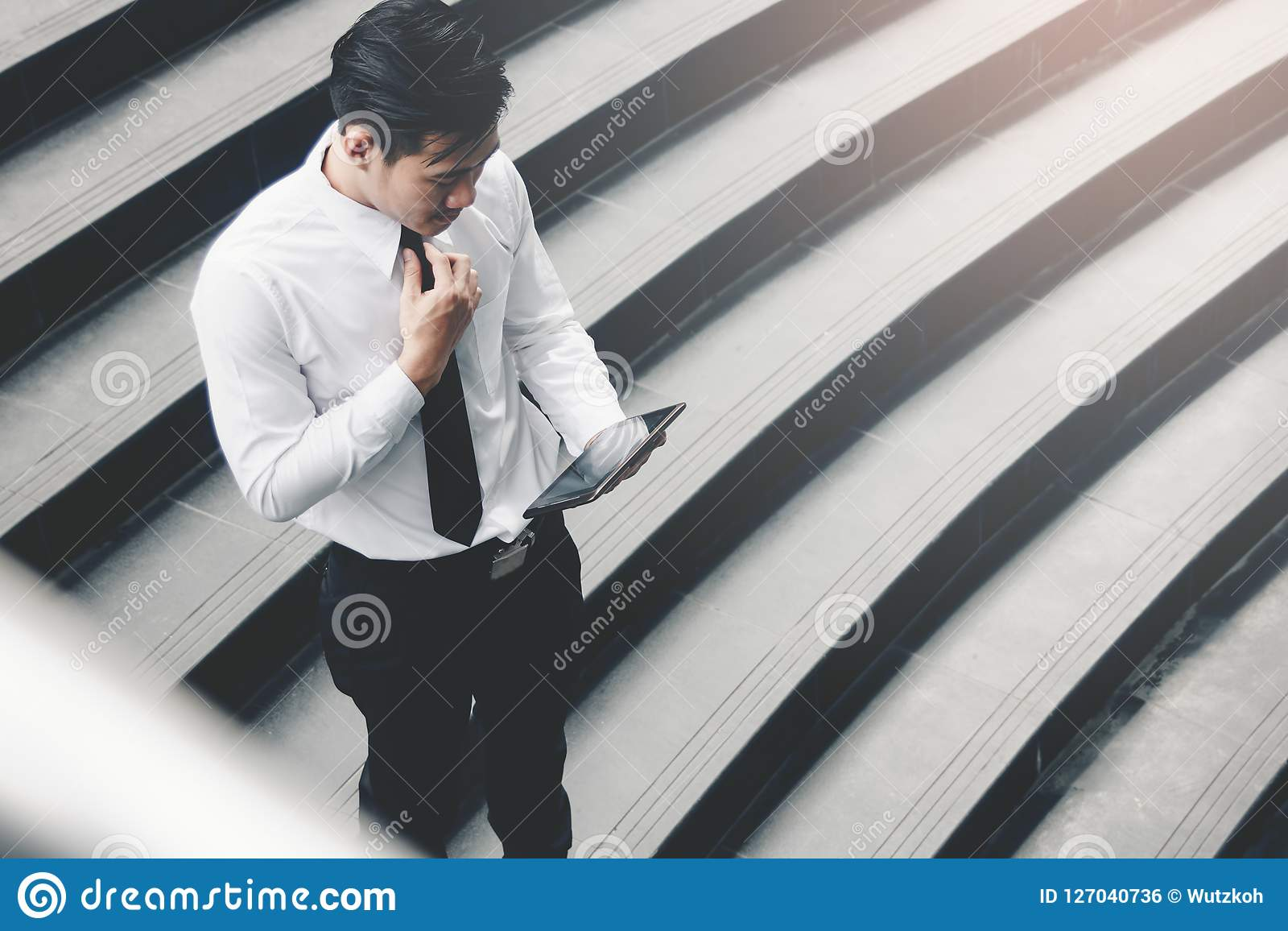 Asian businessman standing on staircase outdoor and using tablet