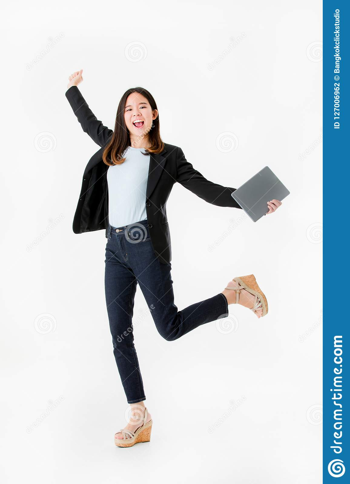 Asian businesswoman in black suit joyful jumping with celebrating successful isolated on white background studio shot.