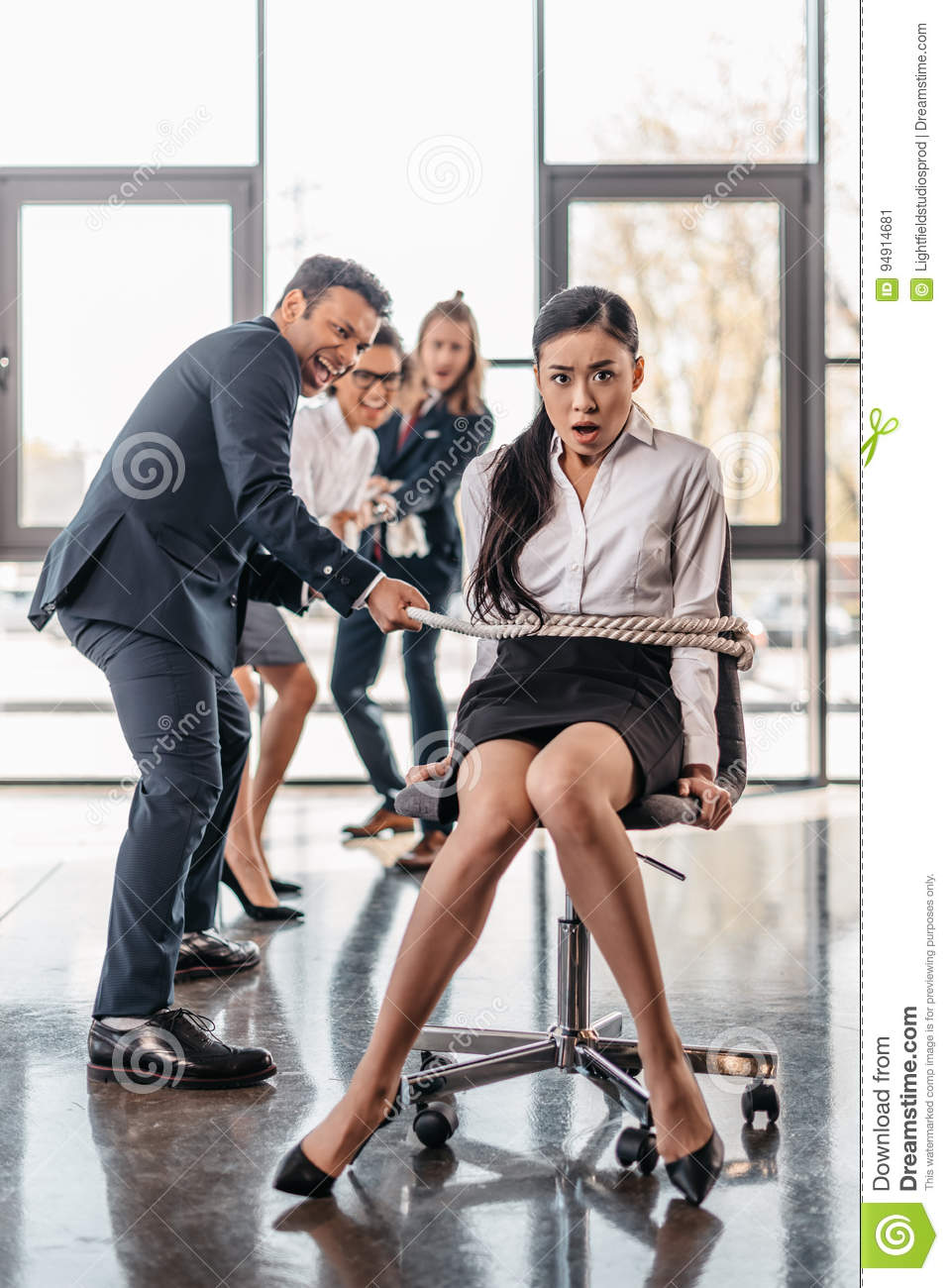 Asian businesswoman bound with rope on chair and multicultural business team pulling her