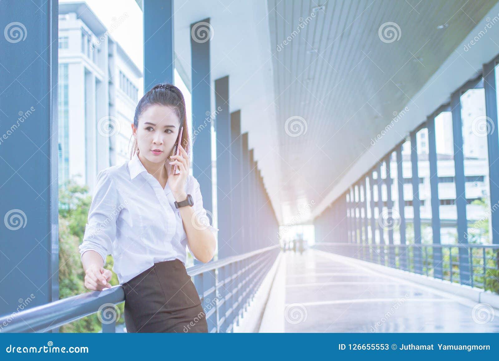 Asian Businesswoman call phone talking , Meetings between executives. between waiting on On sidewalks. Business outdoor