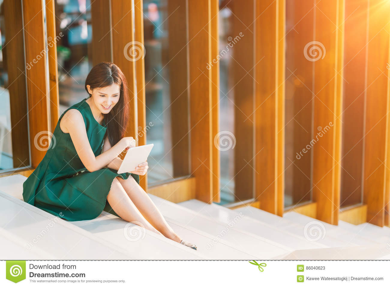 Asian businesswoman or college student using digital tablet at sunset