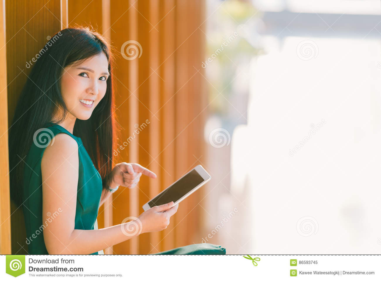Asian businesswoman or college student using and pointing at digital tablet during sunset, at modern office or library
