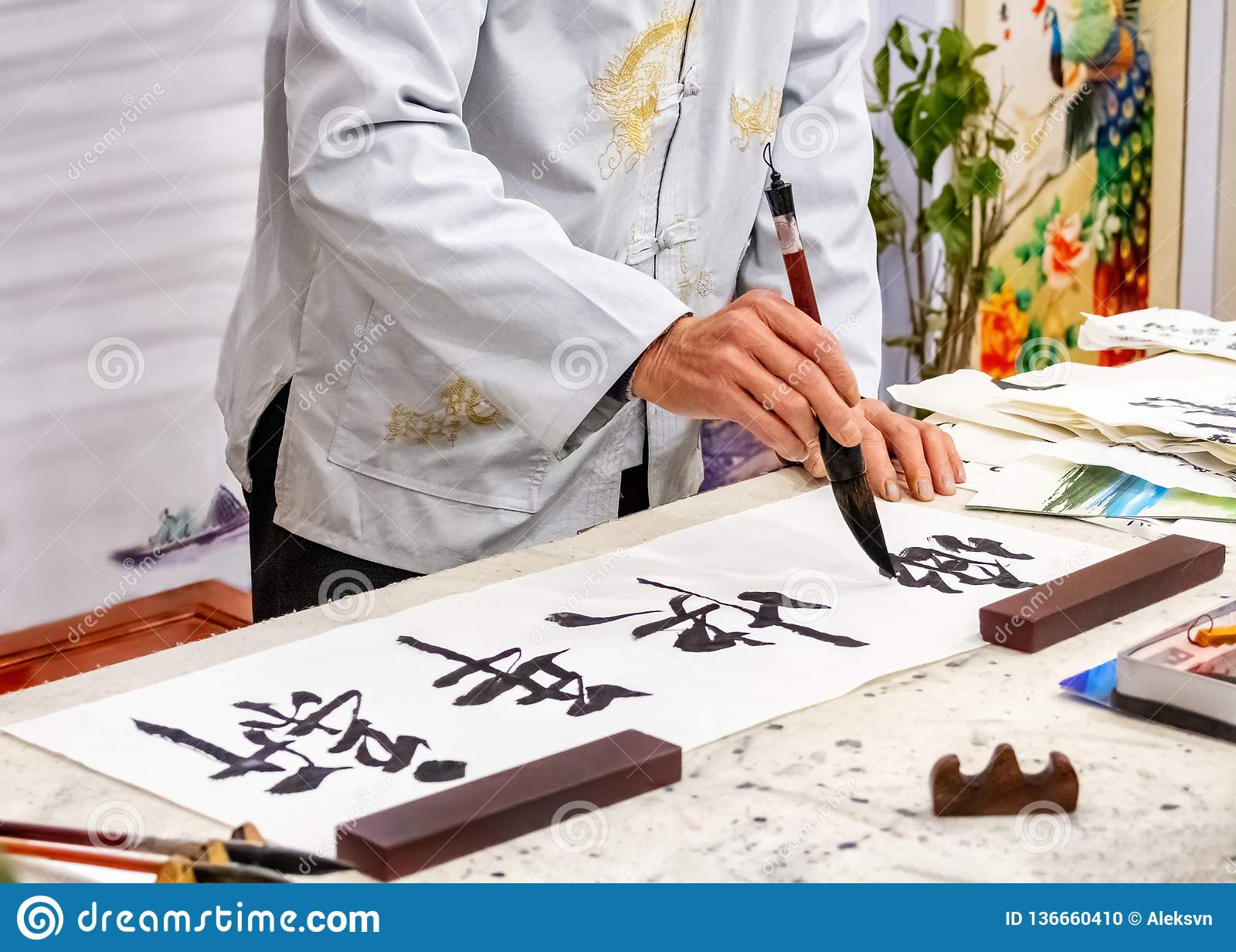 Asian caligraphy. The master of Chinese Caligraphy writes on rice paper characters and hieroglyphs that read Xin nian