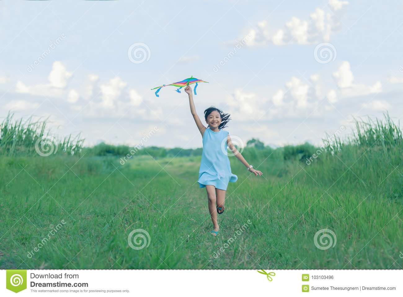 Asian child girl with a kite running and happy on meadow in summer in nature
